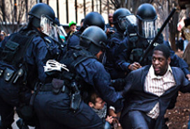 five heavily armored and armed police officers pressing a black man in a business suit to his knees