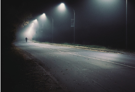 foggy road at night with one man in the far distance walking on the road