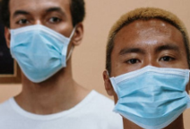 two dark-skinned young men wearing medical masks