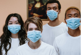 four young adults of different races wearing white t-shirts and masks